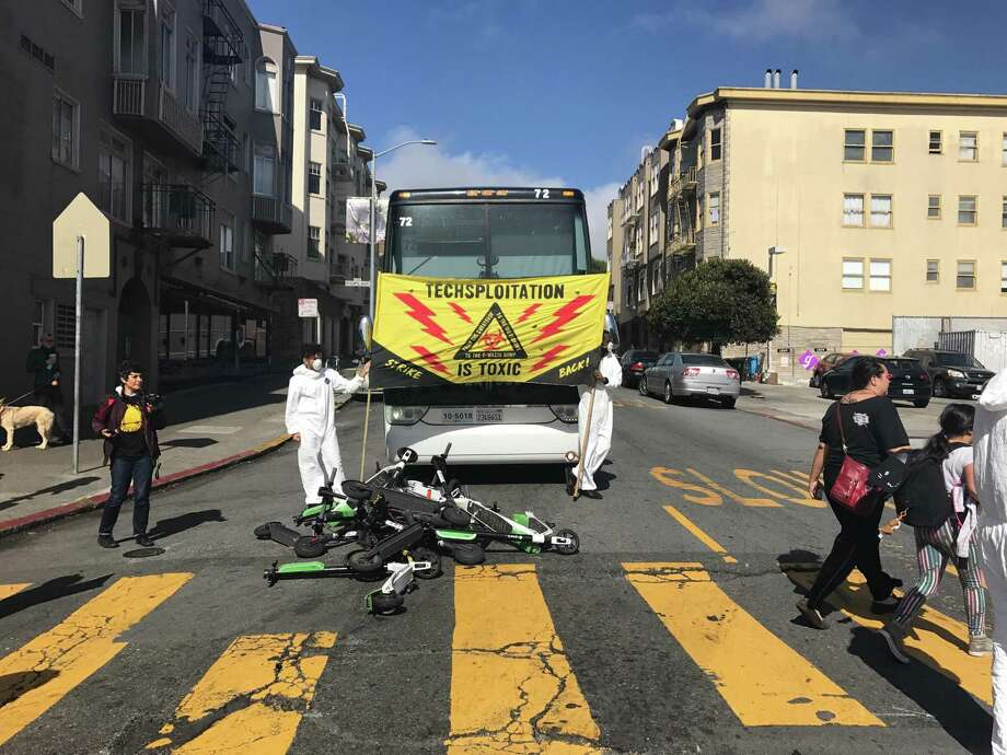 Protesters in the Mission District blocked tech buses from leaving San Francisco on Thursday morning, tossing scooters into the street to waylay the commuters. Photo: Sarah Ravani / The Chronicle