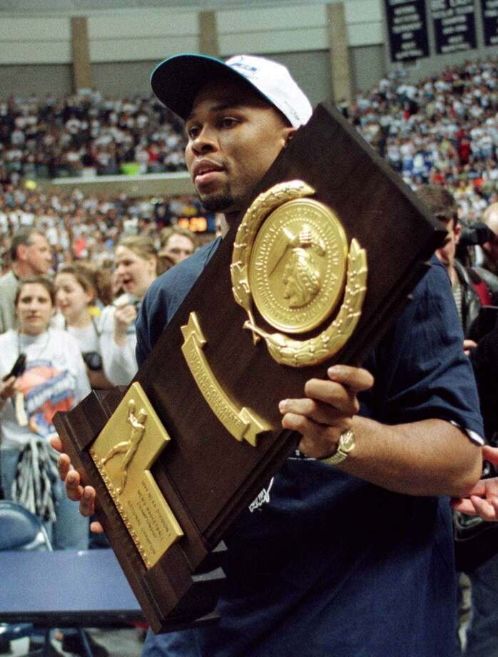 Connecticut basketball team co-captain Ricky Moore carries the winner's trophy during a rally for the team on the UConn campus in Storrs, Conn. Tuesday, March 30, 1999. The UConn men's team defeated Duke 77-74 to win the NCAA Division I men's basketball championship Monday, March 29, 1999.  (AP Photo/Carla Cataldi) Photo: CARLA CATALDI / ST / AP