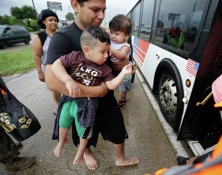 A man carries two children as they board a Metro bus on I 45 south near Edgebrook to be taken to a shelter at the GRB Convention Center Sunday, August 27, 2017, three days after Hurricane Harvey made landfall. Much of the area is flooded. ( Melissa Phillip / Houston Chronicle)