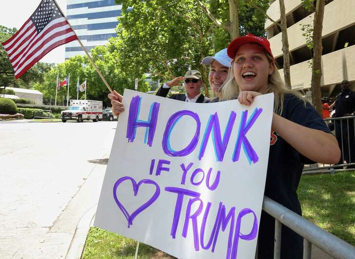 Lauren Voyles, 17, right, and Katy Taylor, 19, hold up signs in support of President Donald Trump, as people gathered outside The St. Regis Houston hotel Thursday, May 31, 2018, in Houston. The president will be speaking at the hotel for  a National Republican Senatorial Committee lunch.