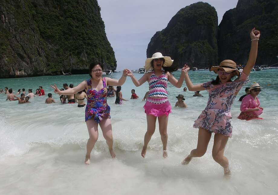 Tourists enjoy Maya Bay. Its beach is closing to give coral reefs and sea life a chance to recover from decades of tourism. Photo: Sakchai Lalit / Associated Press