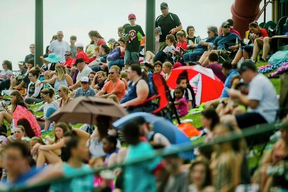 Fans watch from a grassy area along the first base line Wednesday during the Great Lakes Loons' game against South Bend at Dow Diamond. (Katy Kildee/kkildee@mdn.net)