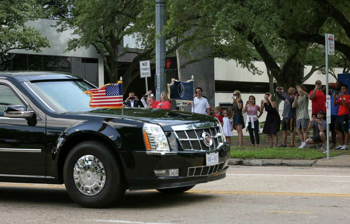 People watch as President Donald Trump's motorcade leaves The St. Regis Houston hotel after speaking at a National Republican Senatorial Committee lunch Thursday, May 31, 2018, in Houston.