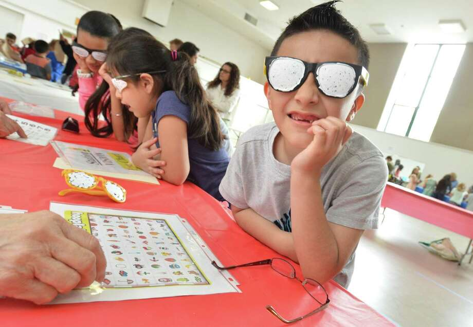 """Marvin Elementary School student John Lopez trys on a pair of modified glasses to see what difficulty focusing and seeing is like at one of the eight stations kids stop at during """"Who says I'm old"""" program at The Marvin senior housing on Thursday May 31, 2018 in Norwalk Conn. The students rotate through several """"stations"""" that are managed by senior residents of The Marvin, as they experience first hand some of the physical and sensory challenges of aging, Mobility challenges, vision changes, taste and smell and hearing changes Photo: Alex Von Kleydorff / Hearst Connecticut Media / Norwalk Hour"""