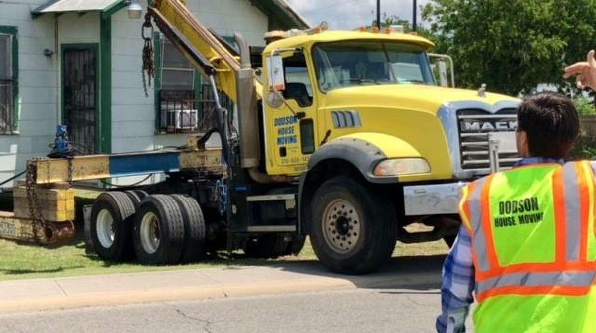 Gator Dodson motions to a truck driver to being the moving of a 1925 house from one lot on IH-35 to another.
