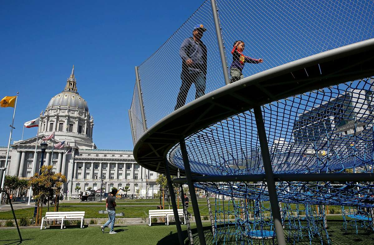 Nino Cunan and his 2-year-old son Kristopher enjoy the newly completed playgrounds in Civic Center Plaza in San Francisco, Ca., on Tues. May 29, 2018. A bond measure is on the ballot that would fund city park improvements and maintenance.