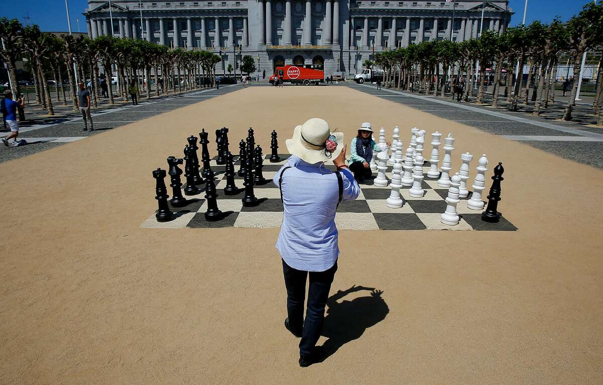 Tourists stop for photos with the oversized chess set in the middle of Civic Center Plaza in San Francisco, Ca., on Tues. May 29, 2018. A bond measure is on the ballot that would fund city park improvements and maintenance.