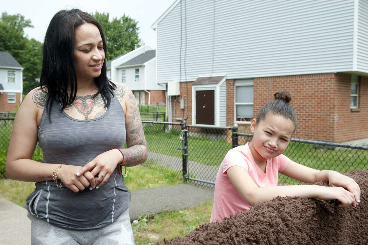 Mildred Arroyo stands with her daughter Melane as she speaks behind their home in the Trumbull Gardens housing complex, in Bridgeport, Conn. May 31, 2018. Arroyo, a long-time resident of Trumbull Gardens, said she feels safer living there with her family after an increased police presence over the past couple of years.