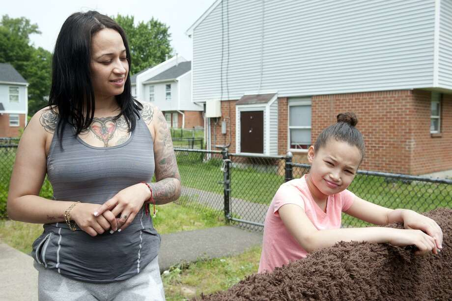 Mildred Arroyo stands with her daughter Melane as she speaks behind their home in the Trumbull Gardens housing complex, in Bridgeport, Conn. May 31, 2018. Arroyo, a long-time resident of Trumbull Gardens, said she feels safer living there with her family after an increased police presence over the past couple of years. Photo: Ned Gerard / Hearst Connecticut Media / Connecticut Post