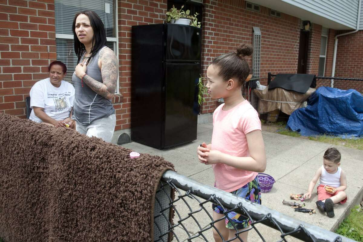 Mildred Arroyo stands with her mother and children as she speaks behind their home in the Trumbull Gardens housing complex, in Bridgeport, Conn. May 31, 2018. Arroyo, a long-time resident of Trumbull Gardens, said she feels safer living there with her family after an increased police presence over the past couple of years.