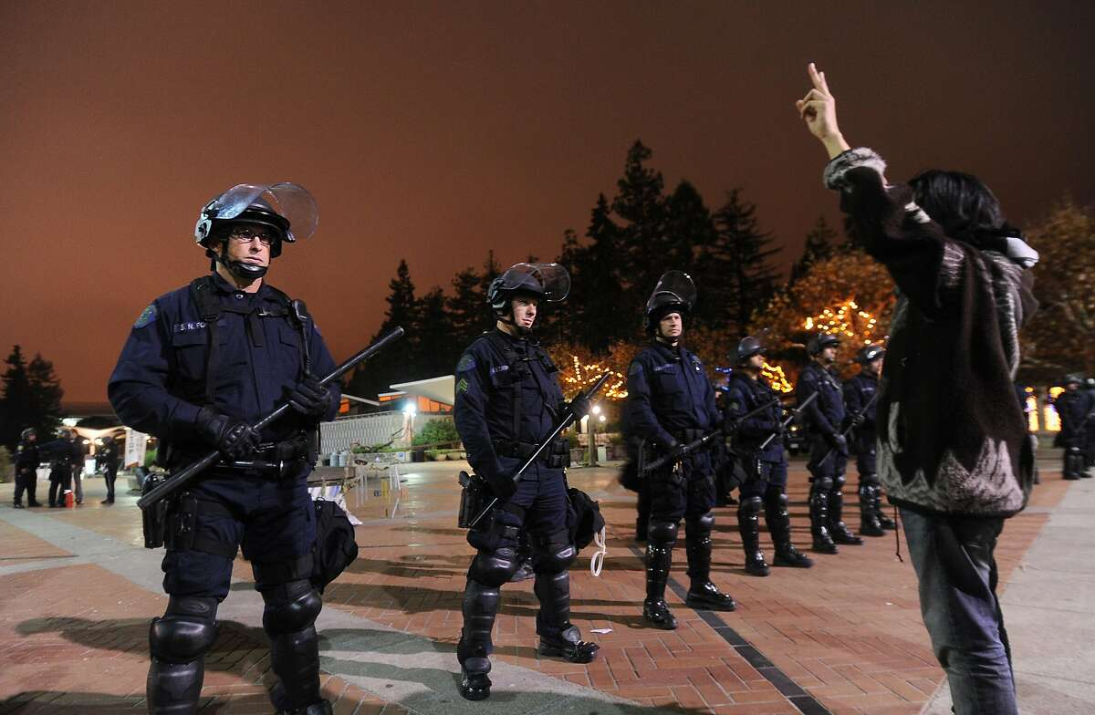 Police surround an Occupy Cal encampment after issuing a five minute warning to vacate on Thursday, Oct. 17, 2011, in Berkeley, Calif. At right, UC Berkeley student Alex Kim was one of two protesters arrested after refusing to leave.