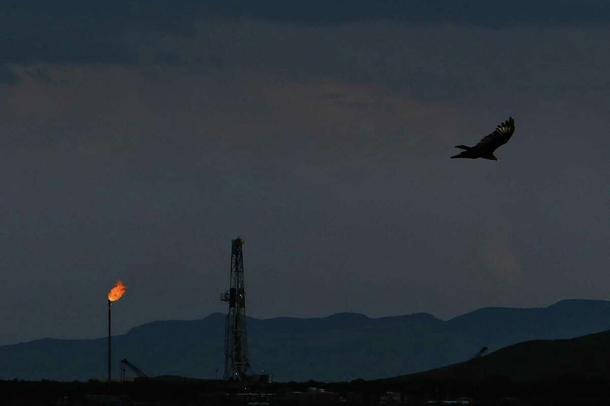 A vulture soars over an Apache Corporation flare and drilling rig north of the Davis Mountains Friday, Sept. 16, 2016 in Balmorhea.Touted as one of the biggest oil and gas discoveries of the decade, Apache Corp.'s Alpine High development is positioned to expand quickly next year and beyond as the company strikes deals to help build pipelines to carry oil and gas from West Texas to port and refining hubs in Houston and Corpus Christi.