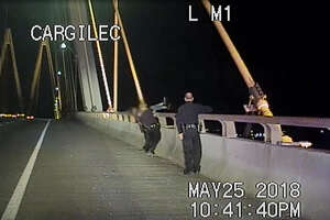 Three La Porte police officers save a woman sitting on Fred Hartman Bridge on May 25.