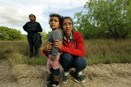 Lirio Funes, 20, holds onto her daughter Melissa Funes, 2, just after being detained by local officials after crossing the U.S. - Mexico border on March 15, 2018 in McAllen, Texas. Photo: Carolyn Cole, MBR / TNS / Los Angeles Times