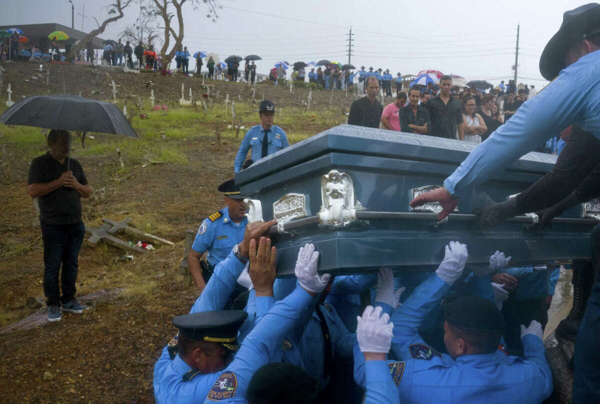 In this Sept. 29, 2017 file photo, police lift the coffin that contain the remains of fellow officer Luis Angel Gonzalez Lorenzo, who was killed while trying to cross a river in his car during the passage of Hurricane Maria, in Aguada, Puerto Rico. A new study contends that many more deaths than normal occurred in Puerto Rico in the three months after Maria devastated the island, mostly because of problems getting medicines or medical care. The research was published online in the New England Journal of Medicine.