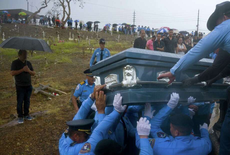 In this Sept. 29, 2017 file photo, police lift the coffin that contain the remains of fellow officer Luis Angel Gonzalez Lorenzo, who was killed while trying to cross a river in his car during the passage of Hurricane Maria, in Aguada, Puerto Rico. A new study contends that many more deaths than normal occurred in Puerto Rico in the three months after Maria devastated the island, mostly because of problems getting medicines or medical care. The research was published online in the New England Journal of Medicine. Photo: Ramon Espinosa, STF / Associated Press / Copyright 2017 The Associated Press. All rights reserved.