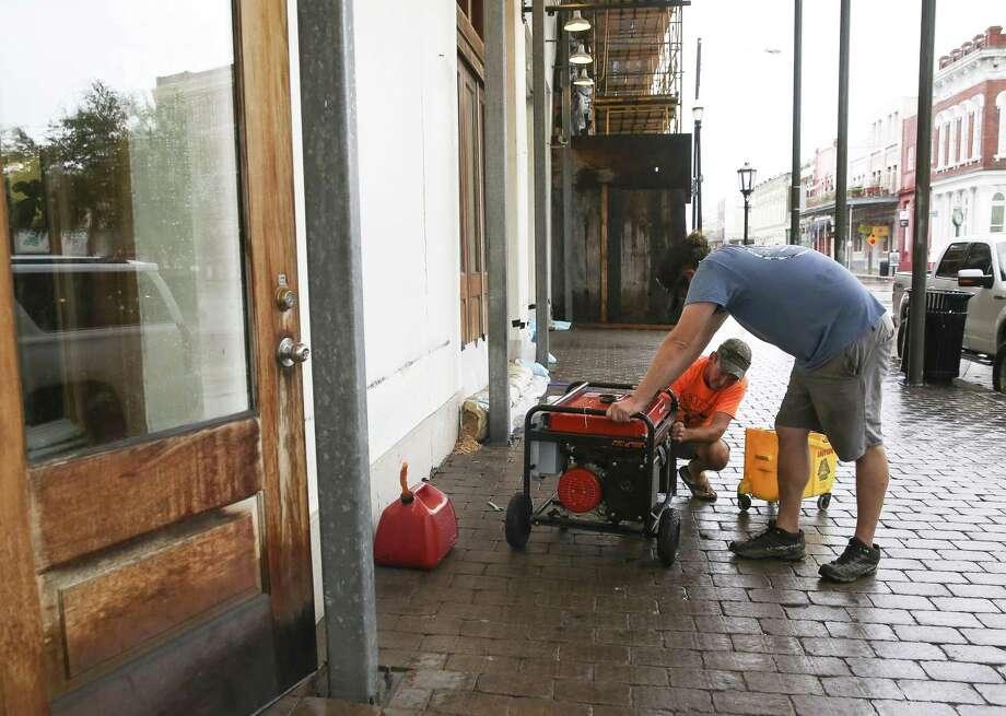 Galvestonians set up a generator during the last-minute hurricane preparations before Hurricane Harvey made landfall last August. Photo: Yi-Chin Lee, Staff / Houston Chronicle / © 2017  Houston Chronicle