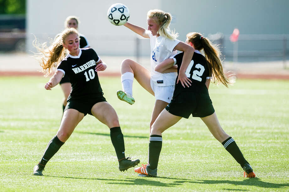 Midland junior Maya Albright, center, fights for possession with Bay City Western junior Mia Bacigalupo, left, and senior Katelynn Campbell, right, during their Division 1 district semifinal game on Thursday, May 31, 2018 at Midland High School. (Katy Kildee/kkildee@mdn.net) Photo: (Katy Kildee/kkildee@mdn.net)