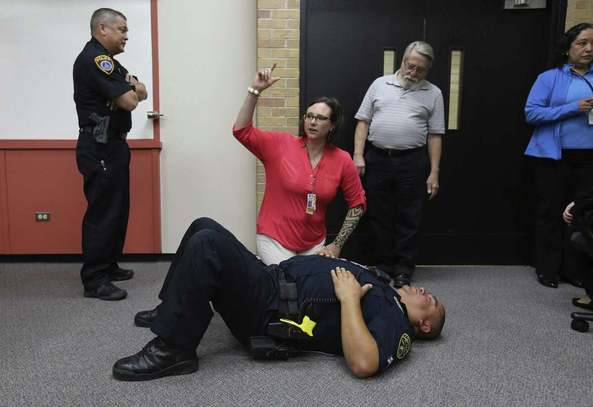 UT Health San Antonio School of Nursing's Colleen Lee, kneeling, and Alamo Community College District Police Officer Jason Santos practice how to revive a person affected by an opioid overdose during a class at UT Health on May 31, 2018. In the photo, Lee pretends to hold a bottle of naloxone nasal spray.