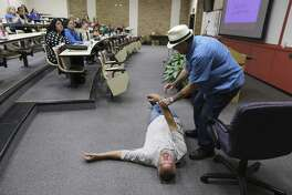 Texas Overdose Naloxone Initiative's Charles Thibodeaux, right, and Mark Kinzly demonstrate how to revive someone from an opioid overdose on May 31. Such training has to be part of a broader initiative to decrease overdose deaths in Bexar County and in Texas.