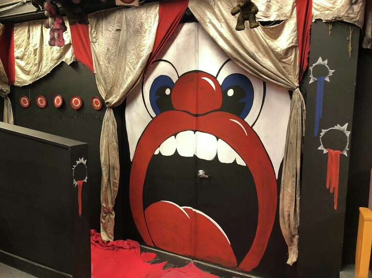 "Jeremy Whittington designed the set for The Public Theater of San Antonio's staging of ""Assassins."" All of the entry points — including the door to the Cellar Theater space — have been masked in ways that evoke carnival attractions and decor."
