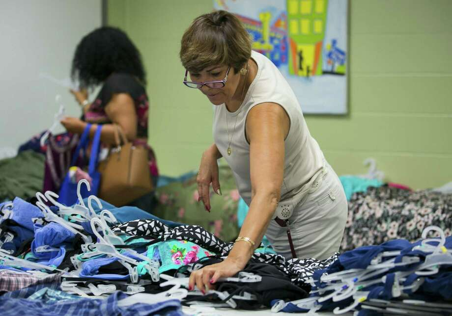 Araceli Ochoa sorts through donations at the BakerRipley Center in Pasadena on Thursday, May 31, 2018. Ochoa assisted neighbors as they picked out clothes and other goods at the center. (Annie Mulligan / For the Houston Chronicle) Photo: Annie Mulligan, Freelance / Annie Mulligan / @ 2018 Annie Mulligan