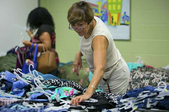Araceli Ochoa sorts through donations at the BakerRipley Center in Pasadena on Thursday, May 31, 2018. Ochoa assisted neighbors as they picked out clothes and other goods at the center. (Annie Mulligan / For the Houston Chronicle)