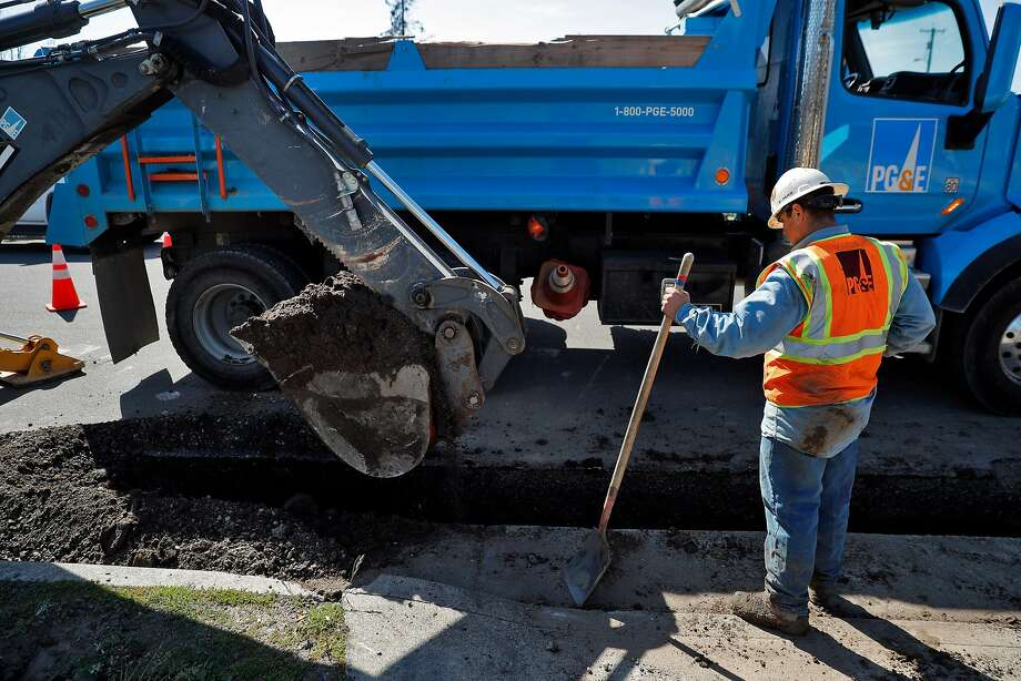 A PG&E worker watches as an excavator removes dirt from a trench as crews and subcontractors began prepping to install underground utility lines in the Coffey Park neighborhood of Santa Rosa in April. The neighborhood was devastated by fire in October. Photo: Carlos Avila Gonzalez / The Chronicle