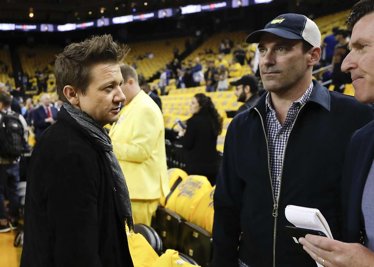 Actors Jeremy Renner, left, and Jon Hamm talk as players warm up before Game 1 of basketball's NBA Finals between the Golden State Warriors and the Cleveland Cavaliers in Oakland, Calif., Thursday, May 31, 2018. (AP Photo/Marcio Jose Sanchez)