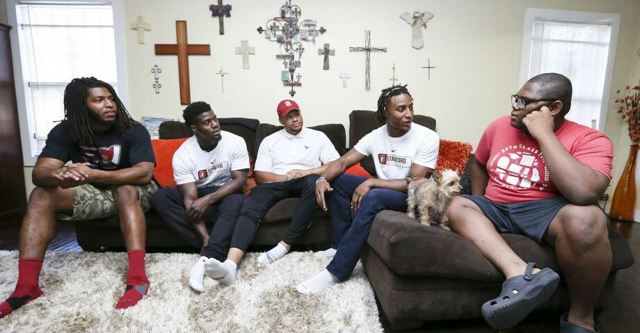 Houston Texans players Peter Kalambayi, from left, Johnson Bademosi, Brennan Scarlett and Justin Reid talk to Micheal Brown, 17, who was accepted to 20 schools and eventually chose Stanford, during a surprise visit with college supplies at his house on Thursday, May 31, 2018, in Houston. The four players are Stanford alumni and they answered Micheal's questions and gave him some advice for college life at Stanford. ( Yi-Chin Lee / Houston Chronicle ) Photo: Yi-Chin Lee/Houston Chronicle