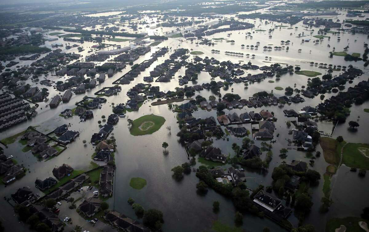 FILE - In this Aug. 31, 2017, file photo, floodwaters from Tropical Storm Harvey surround homes in Port Arthur, Texas. Advocacy groups say Texas is poised to unfairly distribute $5 billion in federal funding provided for housing repairs following Hurricane Harvey, prioritizing wealthy homeowners over poor and working class victims in ways that could constitute racial discrimination. (AP Photo/Gerald Herbert, File)