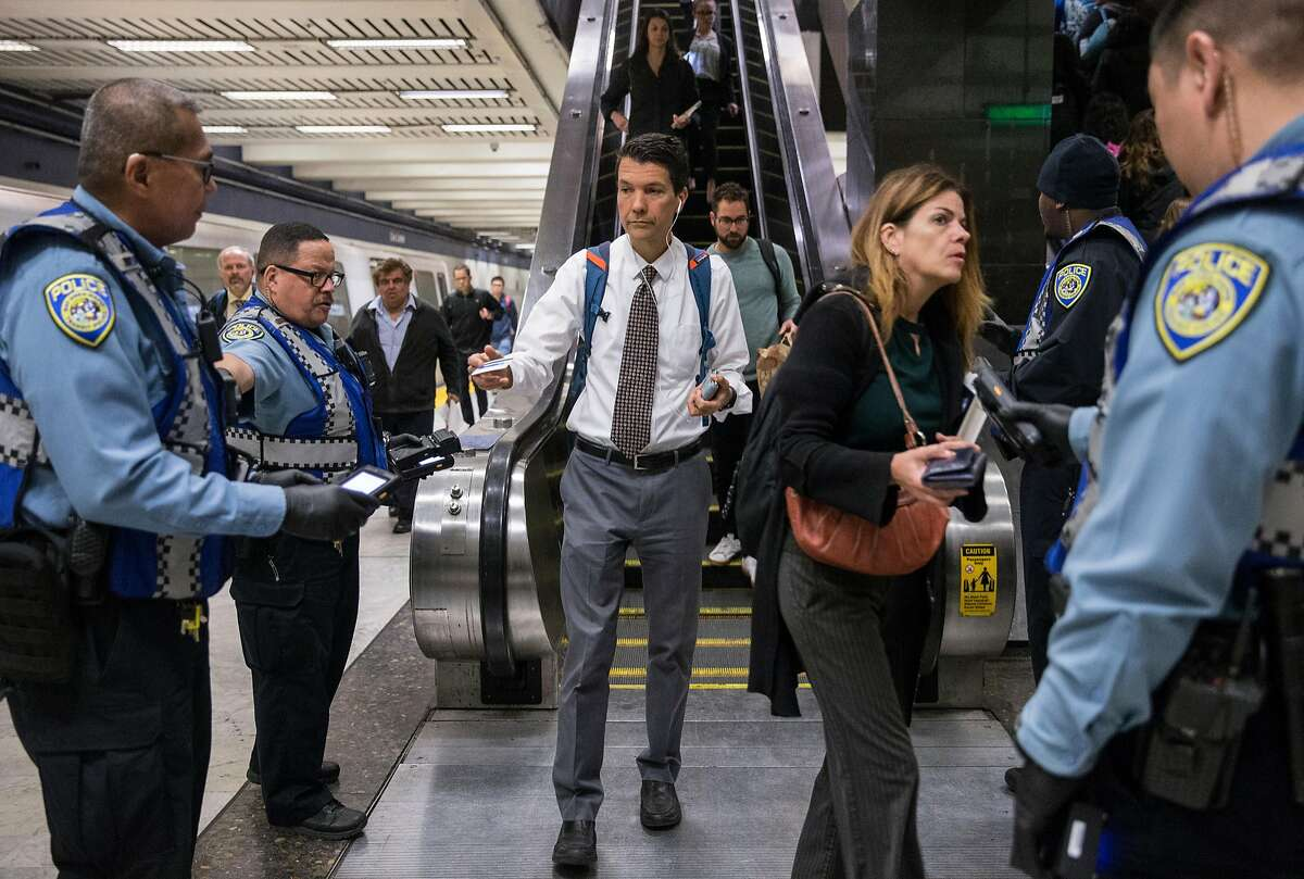 Fare Inspectors patrol the escalator down to the Civic Center Bart Station during the morning commute in San Francisco, Calif. Thursday, May 31, 2018.