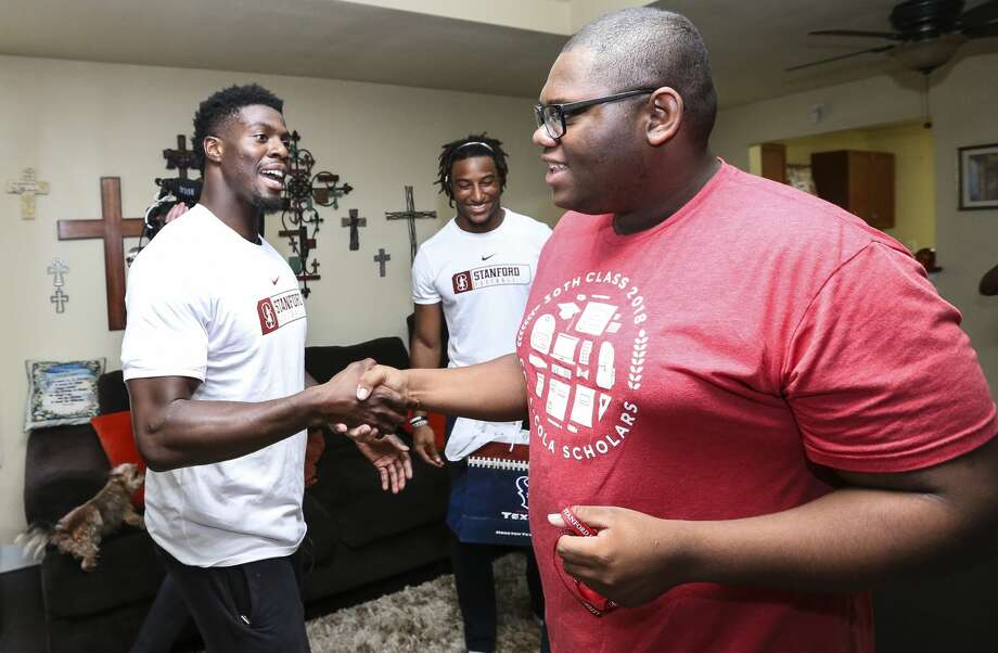 Houston Texans player Johnson Bademosi shakes hands with Micheal Brown, 17, during a surprise visit to Micheal's house with college supplies on Thursday, May 31, 2018, in Houston. The four Texans players who visited are Stanford alumni and they gave Micheal, who was accepted to 20 schools and eventually chose Stanford, some advice for college life at Stanford. ( Yi-Chin Lee / Houston Chronicle ) Photo: Yi-Chin Lee/Houston Chronicle