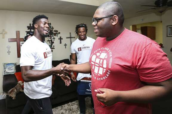 Houston Texans player Johnson Bademosi shakes hands with Micheal Brown, 17, during a surprise visit to Micheal's house with college supplies on Thursday, May 31, 2018, in Houston. The four Texans players who visited are Stanford alumni and they gave Micheal, who was accepted to 20 schools and eventually chose Stanford, some advice for college life at Stanford. ( Yi-Chin Lee / Houston Chronicle )