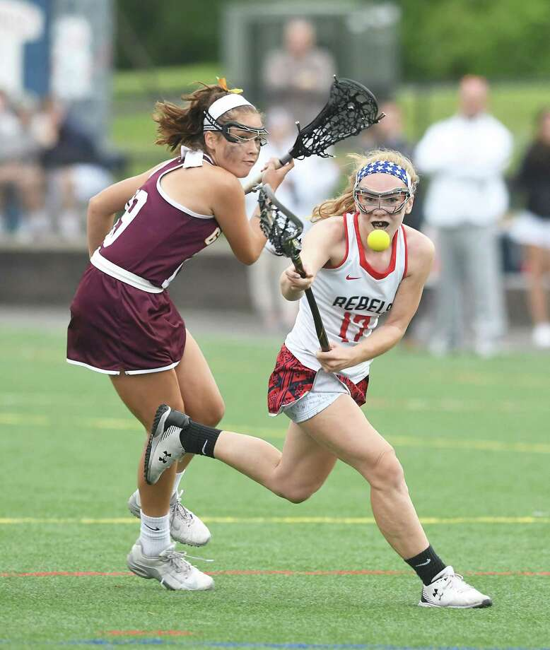 New Fairfield's Sydney Colesworthy makes a pass in front of Granby Memorial's Jaira Paine during the first round of Class S girls lacrosse at New Fairfield, May 31, 2018. Photo: Krista Benson / The News-Times Freelance