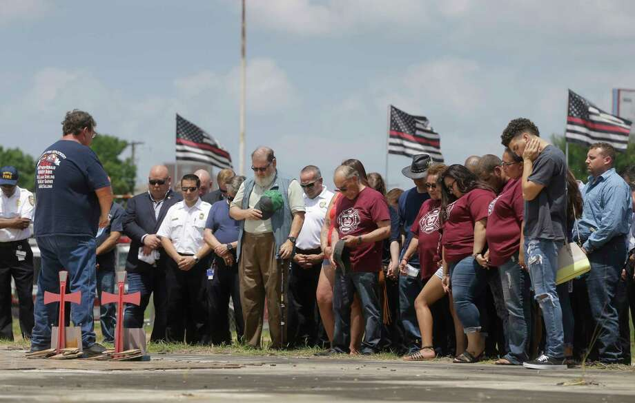 """People pray Thursday, May 31, 2018, in Houston at the site of the fire at the Southwest Inn, 6855 Southwest Fwy., where they gathered to honor firefighters killed five years ago. Robert Bebee, Robert Garner, Mathew Renaud, and Anne Sullivan were the four firefighters who died in the blaze. Another firefighter, Captain William """"Iron Bill"""" Dowling, who suffered severe injuries and lost both his legs passed away on March 7, 2017. Photo: Melissa Phillip, Houston Chronicle / © 2018 Houston Chronicle"""