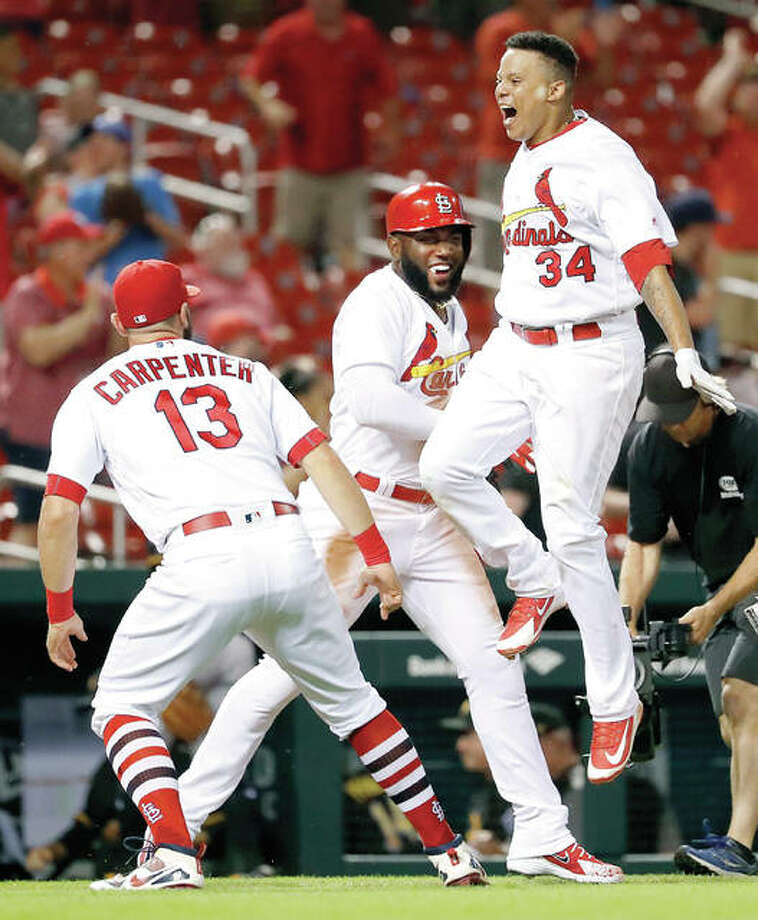 The Cardinals' Yairo Munoz (34) is congratulated by teammates Marcell Ozuna and Matt Carpenter (13) after hitting a walk-off home run against the Pirates Thursday night in St. Louis. The Cardinals won 10-8. Photo:       AP