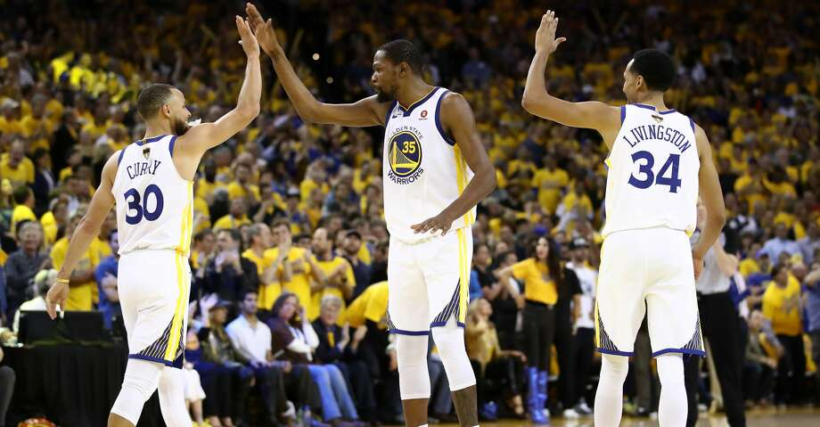 OAKLAND, CA - MAY 31:  Stephen Curry #30 of the Golden State Warriors celebrates with Kevin Durant #35 and Shaun Livingston #34 against the Cleveland Cavaliers in overtime during Game 1 of the 2018 NBA Finals at ORACLE Arena on May 31, 2018 in Oakland, California. NOTE TO USER: User expressly acknowledges and agrees that, by downloading and or using this photograph, User is consenting to the terms and conditions of the Getty Images License Agreement.  (Photo by Ezra Shaw/Getty Images) Photo: Ezra Shaw/Getty Images