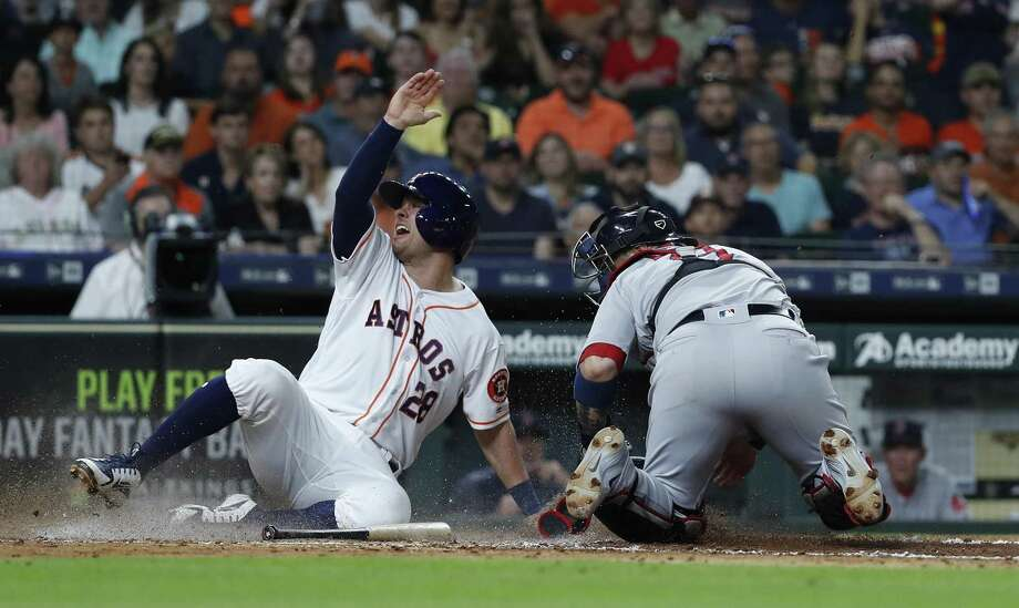 Astros first baseman J.D. Davis, left, beats the throw and the tag of catcher Sandy Leon to score a run against the Red Sox on Thursday night at Minute Maid Park. Photo: Karen Warren, Staff / Houston Chronicle / © 2018 Houston Chronicle