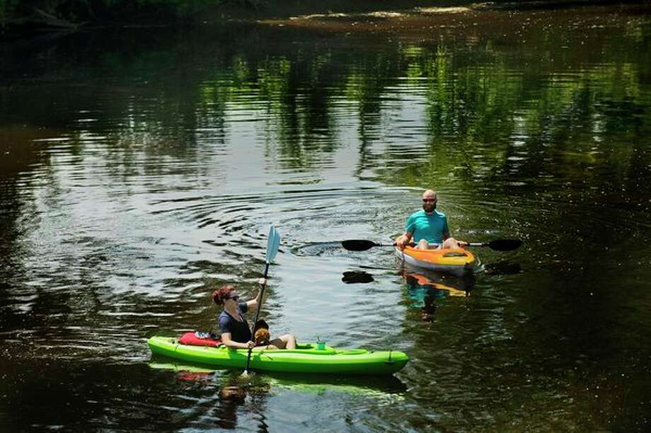 Two people kayak along the Chippewa River near the Tridge with their dog in tow on Tuesday afternoon. Temperatures in Midland reached 81 degrees that day. (Katy Kildee/kkildee@mdn.net)