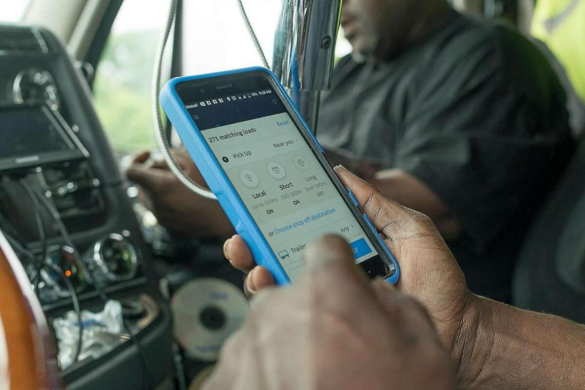 Amir Shah, a truck owner-operator of Traveloko, at the cab of a freight truck look at his Uber Freight app on his mobile phone in Cameron, Texas on Thursday May 24, 2018. Mr. Shah runs most of his business entirely through Uber Freight.