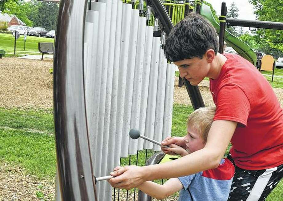 Hayden Leonard (left), 15, helps his brother, Greyson Leonard, 6, play music Thursday on a new toy in Community Park.