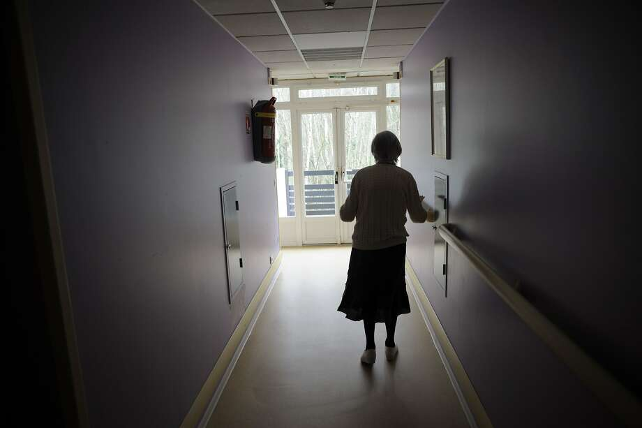 An Illinois family is suing a nursing home and two of its former employees after a video appears to show caregivers taunting a 91-year-old woman. Photo - In this file photo taken on March 18, 2011 a woman, suffering from Alzheimer's desease, walks in a corridor in a retirement house.  Photo: SEBASTIEN BOZON, AFP/Getty Images