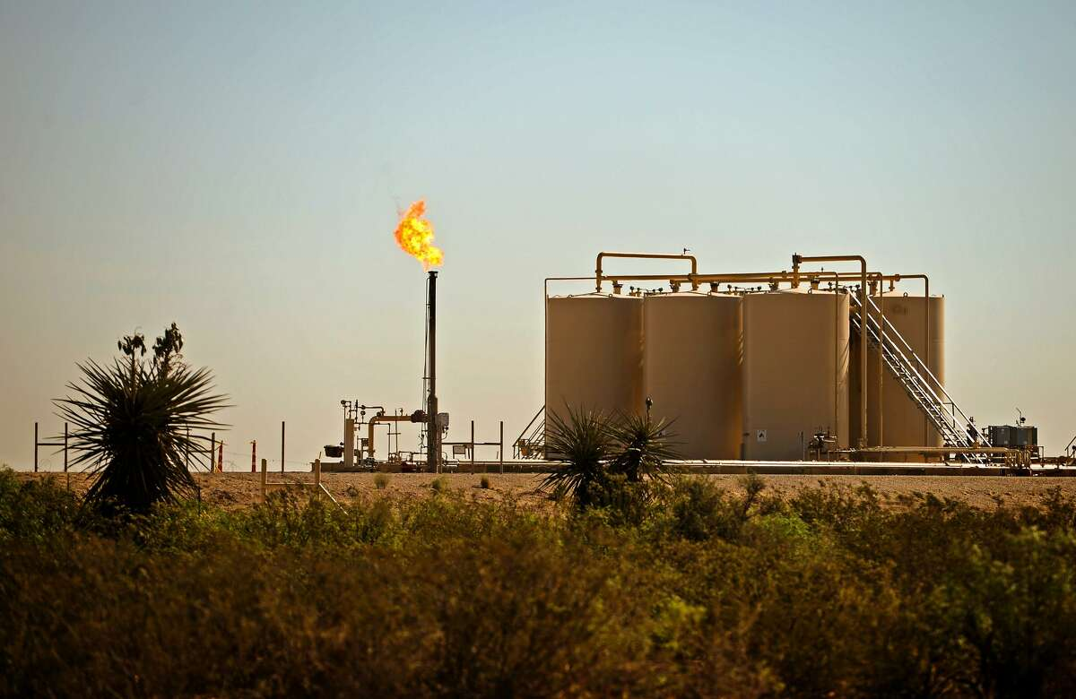 A natural gas flare is visible near storage tanks May 30, 2018, in Reeves County, Texas. Global demand for natural gas fell 2.5 percent in 2020, despite the economic lockdowns caused by the coronavirus pandemic, according to a new report.
