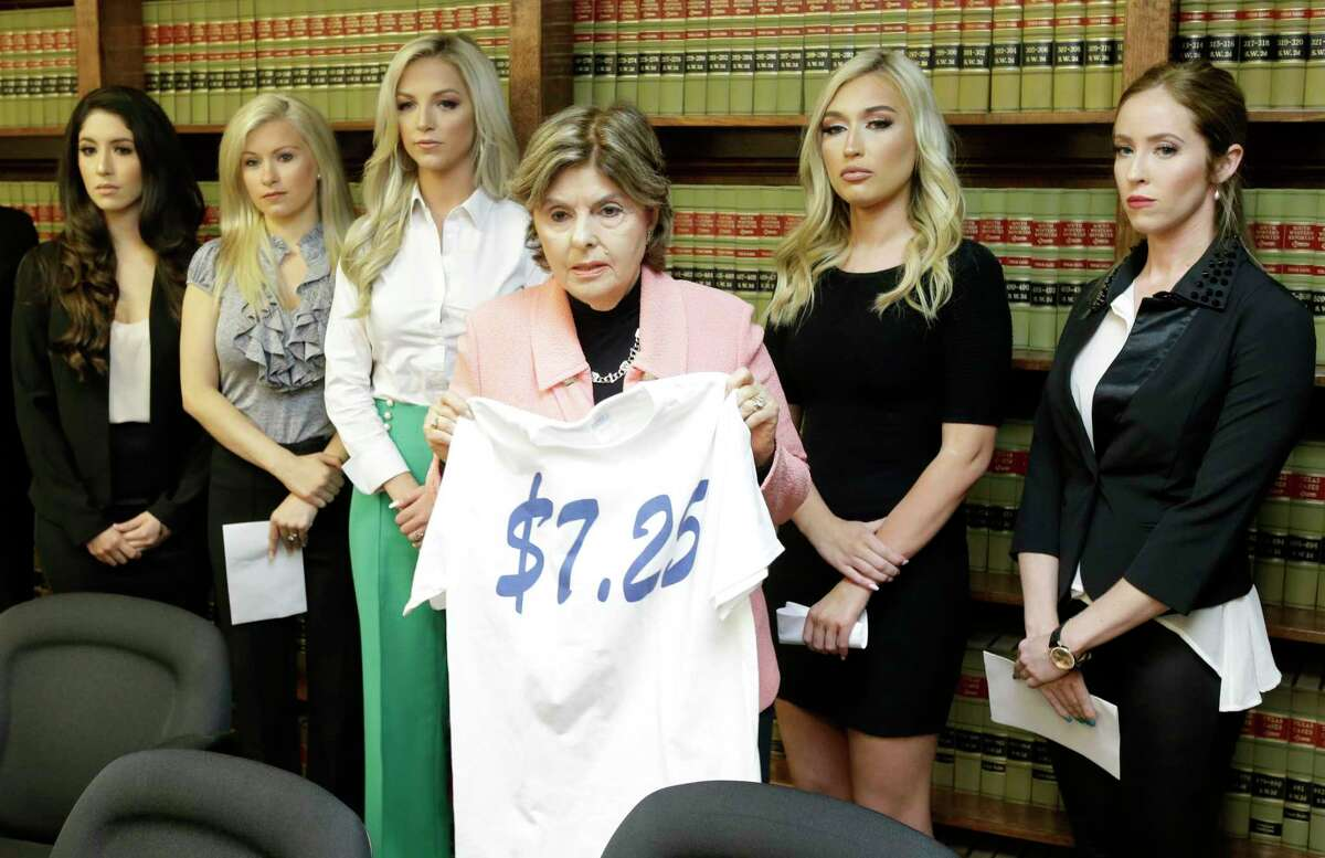 Attorney Gloria Allred stands among former Houston Texans cheerleaders Ashley Rodriguez, left, Morgan Wiederhold, Kelly Neuner, Hannah Turnbow, and Ainsley Parish, right, holding up a shirt printed with $7.25, the amount she says the former cheerleaders where paid per hour, as she speaks during a press conference announcing a lawsuit on behalf of the five the former cheerleaders shown at the law offices of Kimberley Spurlock, 17280 West Lake Houston Parkway, in Humble, Friday, June 1, 2018.