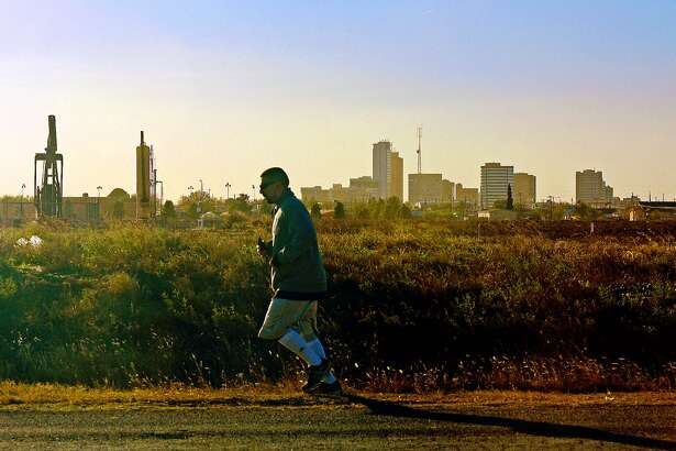 A jogger travels along Fairgrounds Road past a pumpjack and the downtown skyline on Nov. 21, 2017. James Durbin/Reporter-Telegram