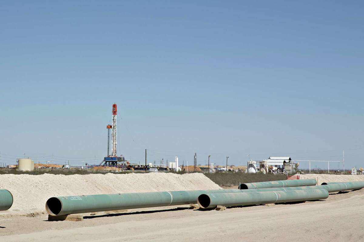 Sections of pipeline lie on the ground near an oil drill rig in the Permian Basin near Pyote, Texas, on March 2, 2018.