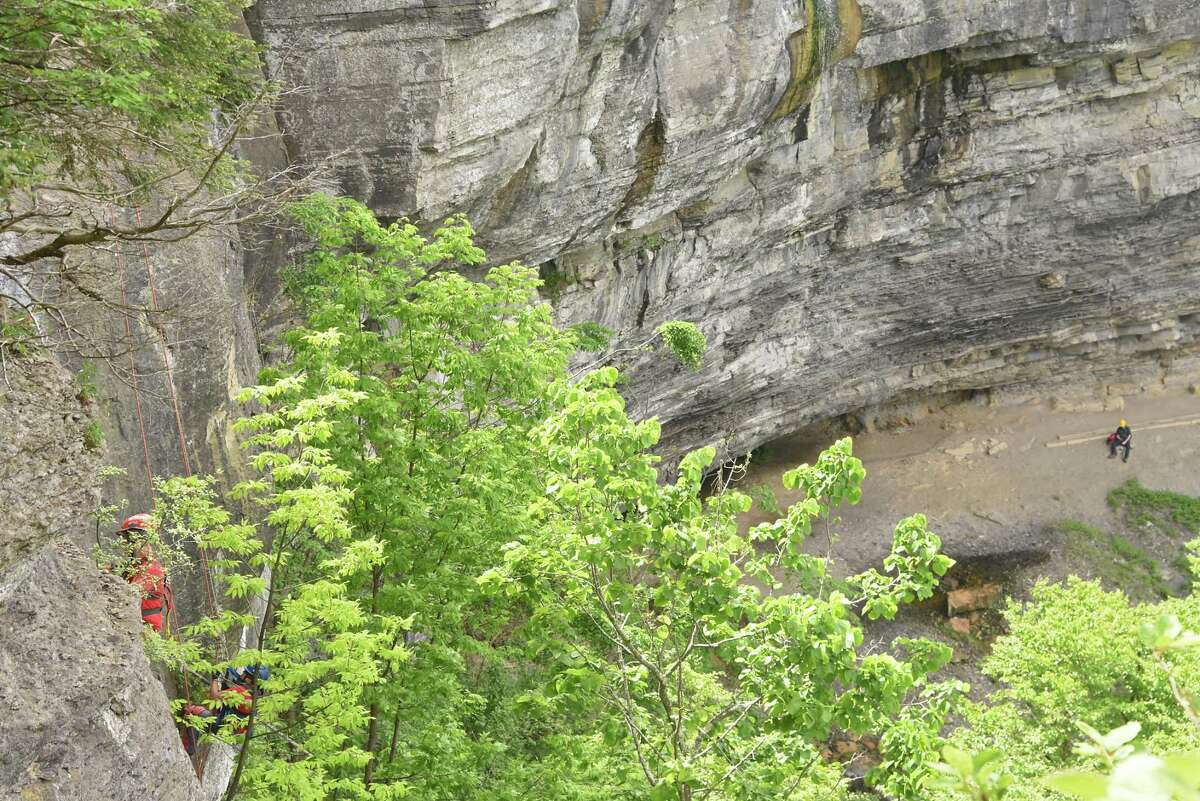 Members of New York State Parks Recreation & Historic Preservation scaling team rappel down the rocky cliff above Indian Ladder Trail at John Boyd Thacher State Park on Thursday, May 31, 2018 in New Scotland, N.Y. Another member watches from below as a spotter. The scaling team, out of Ithaca, was removing loose rocks to prevent future injuries to hikers below. (Lori Van Buren/Times Union)