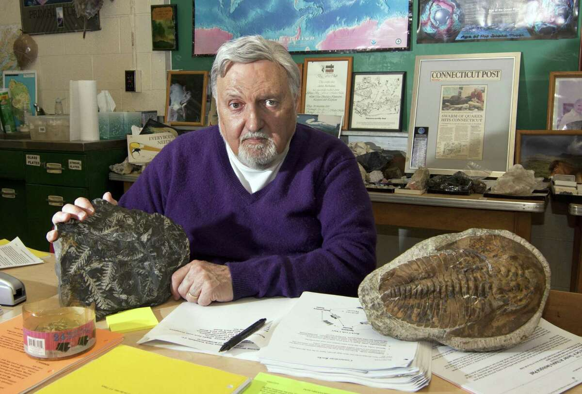 """Professor John Nicholas, aka """"Doc Rock,"""" who will be retiring after a career spanning a half-century, poses in his classroom at the Charles A. Dana Hall of Science on the campus of University of Bridgeport in Bridgeport, Conn., on Tuesday May 15, 2018."""