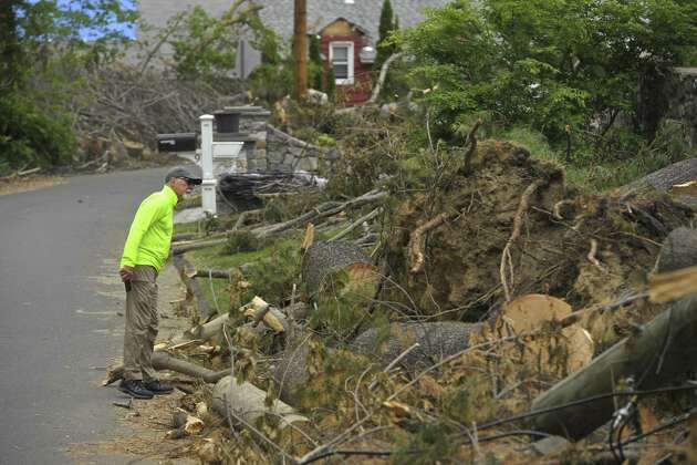 George Bailey looks over the remaining storm damage trees on his Pocono Point Road property, on Thursday, May 31, 2018, in Danbury, Conn.